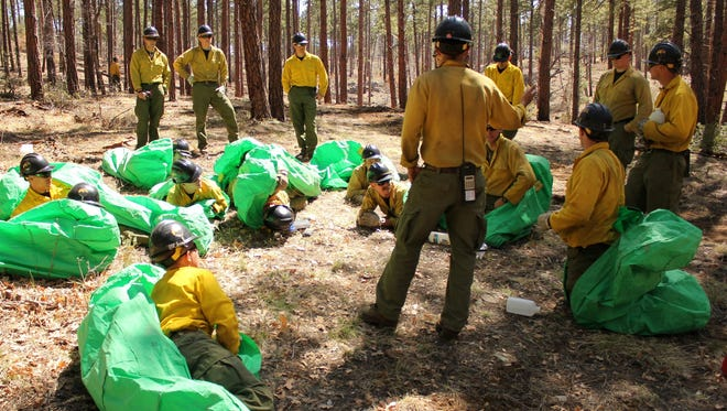 In this 2012 photo provided by the Cronkite News, Phillip Maldonado, a squad leader with the Granite Mountain Hotshots, trains crew members on setting up emergency fire shelters.