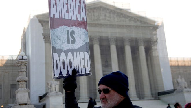 Fred Phelps Jr., of Topeka, with the Westboro Baptist Church, holds a sign in front of the Supreme Court in Washington.