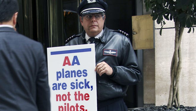 American Airlines pilot Sam Mayer pickets in front of a hotel where American Airlines CEO Tom Horton talked with reporters on Oct. 8, 2012. Horton was in New York to help welcome Qatar Airways as the newest member of the oneworld frequent-flier alliance.