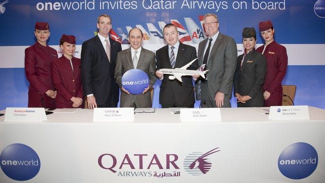 Qatar Airways CEO Akbar Al Baker is seen holding the round 'oneworld' logo at a news conference announcing his airline's invitation to the frequent-flier alliance. He's flanked by American Airlines CEO Tom Horton (immediately to the left) and by Willie Horton (right), the CEO of British Airways and Iberia parent of IAG.