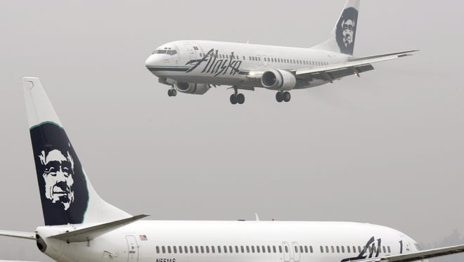 An Alaska Airlines plane comes in for a landing as another taxis out at Seattle-Tacoma International Airport on Jan. 17, 2009.