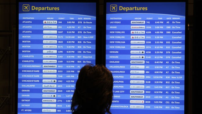 A passenger checks the departures board at Pittsburgh International Airport on Wednesday, Oct. 31, 2012. Travel in the Northeast creaked back into motion on Wednesday, a grinding, patchy recovery that made it clear that stranded travelers will struggle to get around for days to come.