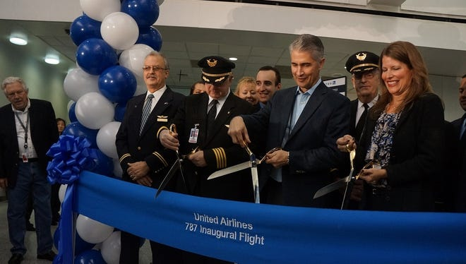 United Airlines CEO Jeff Smisek (center) is joined by United crew in cutting the ribbon prior to the carrier's first-ever revenue flight on the Boeing 787 Dreamliner.