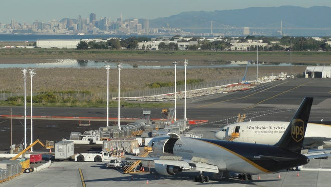 UPS cargo aircraft are serviced at Oakland International Airport. The skyline of the city of San Francisco is seen in the background.