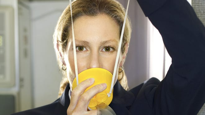 An undated image of a flight attendant demonstrating the use of an oxygen mask.