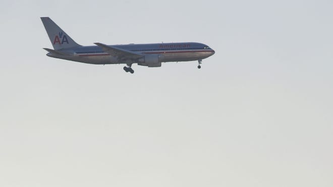 An American Airlines plane flies over the Interstate 405 freeway upon approach to Los Angeles International Airport on Nov. 25, 2009.
