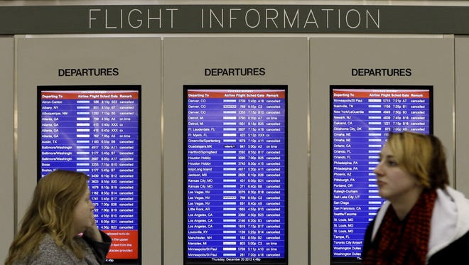 A flight information screen displays canceled flights as passenger walk at Midway airport in Chicago on Thursday, Dec. 20, 2012.