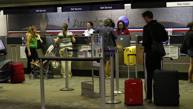 Travelers check-in baggage at Sky Harbor International Airport in Phoenix, Arizona.