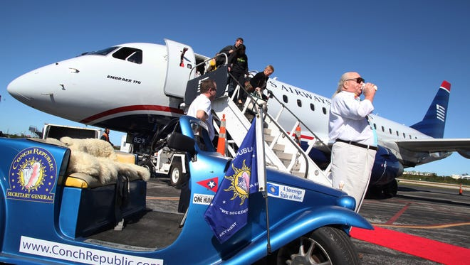 Delta Air Lines gives Key West its longest flight ever: Delta Air Lines and US Airways began two new routes at Key West International Airport. The routes link Key West with the Northeast, and — airport officials say — give the small Florida airport the longest regularly scheduled commercial flight in its history. In this photo provided by the Florida Keys News Bureau, Peter Anderson, right, blows a conch shell on Dec. 22, as passengers exit a US Airways plane in Key West, Fla. The flight marked the arrival of the first nonstop flight from Washington's Reagan National Airport.