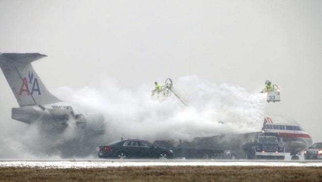 In this file photo from Feb. 9, 2011, DFW Airport workers deice an American Airlines airplane.
