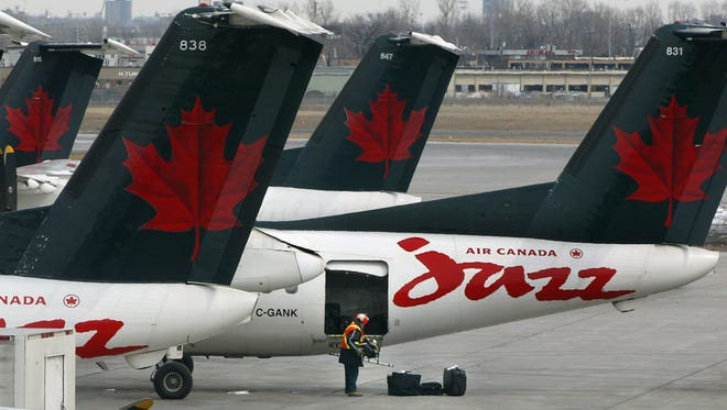 An Air Canada employee unloads luggage from an aircraft of its regional carrier Jazz at Montreal's Dorval airport Tuesday, April 1, 2003. Most of Jazz's planes now fly under a different paint scheme
