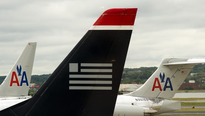 A US Airways plane sits within view of two American Airlines planes at Ronald Reagan Washington National Airport on April 23, 2012.
