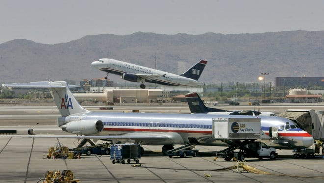 In this June 23, 2008, file photo, a US Airways jet takes off as an American Airlines sits at Sky Harbor International Airport in Phoenix.