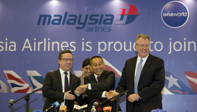Malaysia Airlines Group CEO Ahmad Jauhari Yahya (center) celebrates with Qantas CEO Alan Joyce (left) and oneworld CEO Bruce Ashby during the signing ceremony of the national carrier'??s membership into the oneworld alliance in Kuala Lumpur on Jan. 31, 2013.