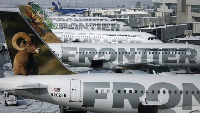 Frontier Airlines jetliners sit at the A concourse at Denver International Airport on Feb. 22, 2010.