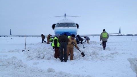Workers at Wichita Mid-Continent Airport work to dig out a United Express Canadair CRJ-700 regional jet that got stuck on a snow-covered taxiway on Thursday, Feb. 21, 2013.