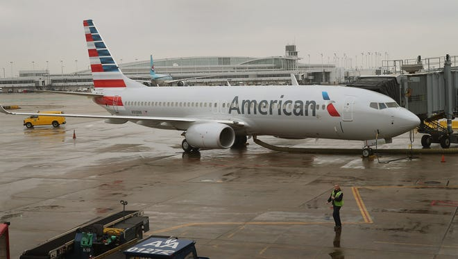 A new American Airlines 737-800 aircraft featuring the airline's new paint job sits at a gate at Chicago O'Hare Airport on Jan. 29, 2013.