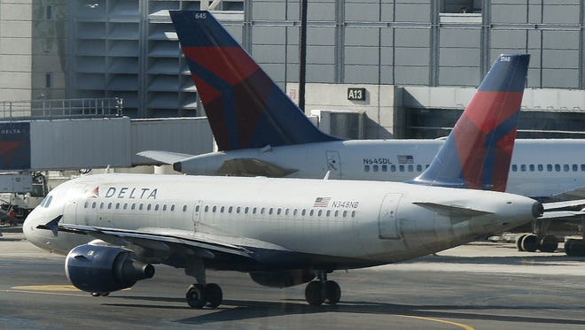 A Delta Air Lines plane taxis past a gate at Boston's Logan International Airport on Jan. 24, 2012.