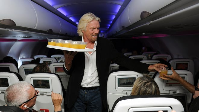Virgin Group founder Richard Branson passes out beverages aboard a flight from New York to San Francisco last year. Passengers can now send each other drinks on Virgin America flights. Branson will likely not be passing those out.