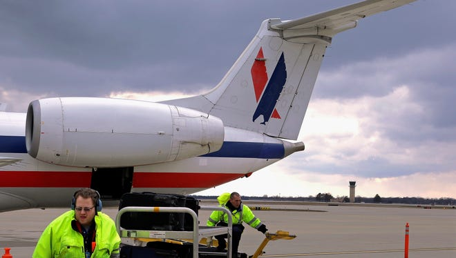In this March 12, 2013 photo, baggage handlers unload an American Eagle jet after it landed at the Abraham Lincoln Capital Airport in Springfield, Ill.