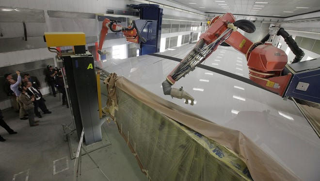 This May 29, 2013 photo shows Boeing's new robot-painting machines in Everett, Wash.  These new robot-painting machines can wash, apply solvent to remove dirt, rinse and then spray two different paint types. They reach even into complex spaces inside the open wing root that must be painted for corrosion protection.