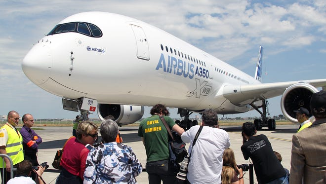 In this photo from June 14, 2013, press greet the Airbus A350 after its maiden flight at Blagnac airport near Toulouse, France.