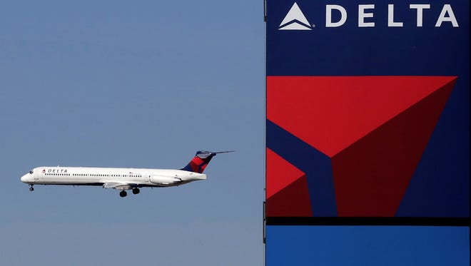 In this April 6, 2013, photo, a Delta jet flies past the company's billboard at Citi Field in New York.