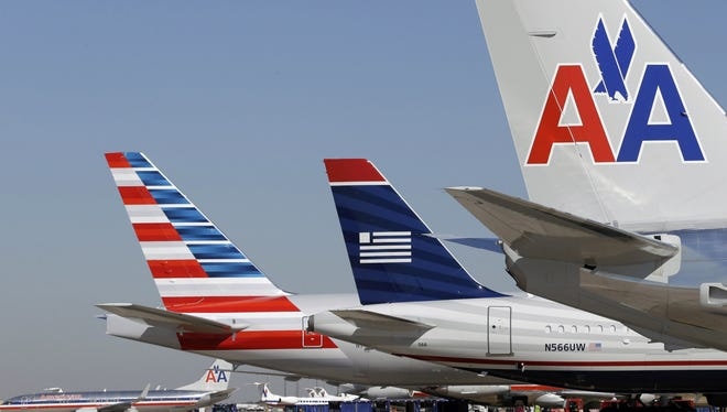 In this Thursday, Feb. 14, 2013, file photo, US Airways and American Airlines planes are seen at Dallas/Fort Worth International Airport.