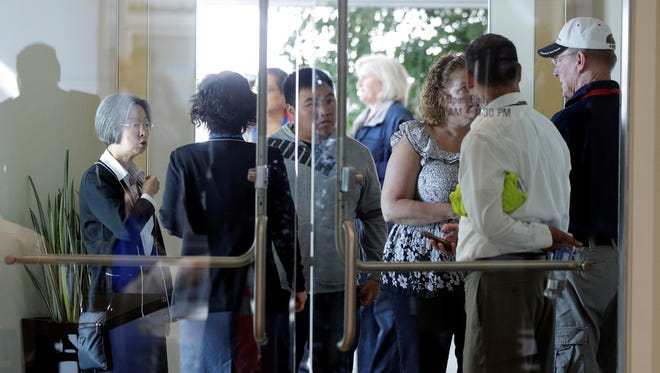 People speak in The Reflection Room where friends and relatives of Asiana Flight 214 passengers await news following the crash of the passenger jet at the San Francisco International Airport.