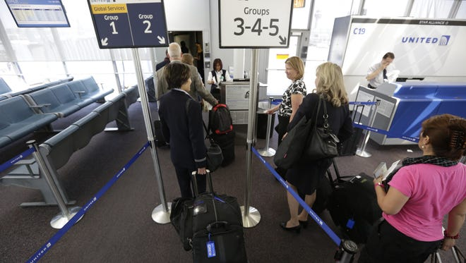 This file photo from May 8, 2013, shows fliers waiting to board a United Airlines flight at Chicago O'Hare International Airport.