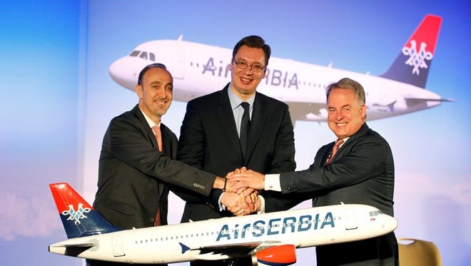 Dane Kondic (left), CEO of new Air Serbia company; Serbia's deputy Prime Minister Aleksandar Vucic (center) and Etihad CEO James Hogan, join hands after signing a partnership deal in Belgrade on Aug 1, 2013.