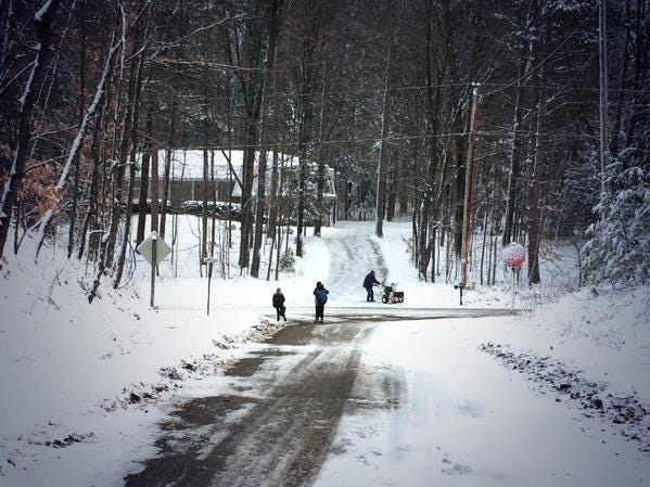 Children wait for the school bus while a neighbor clears snow from a driveway in Pittsfield on Tuesday morning.