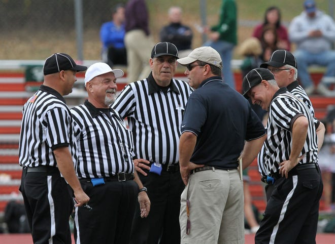 Referees talk with Greeley football coach Tim Sullivan during a football game between Greeley and Yorktown on Oct. 3 at Horace Greeley High School in Chappaqua.