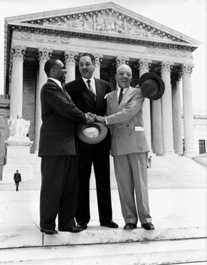 """This May 17, 1954 file photo shows, from left, George E.C. Hayes, Thurgood Marshall, and James M. Nabrit joining hands as they pose outside the Supreme Court in Washington.  The three lawyers led the fight for abolition of segregation in public schools before the Supreme Court, which ruled today that segregation is unconstitutional. On May 17, 1954, a hushed crowd of spectators packed the Supreme Court, awaiting word on Brown v. Board of Education, a combination of five lawsuits brought by the NAACP's legal arm to challenge racial segregation in public schools. The high court decided unanimously that """"separate but equal"""" education denied black children their constitutional right to equal protection under the law, effectively removing a cornerstone that propped up Jim Crow, or state-sanctioned segregation of the races."""