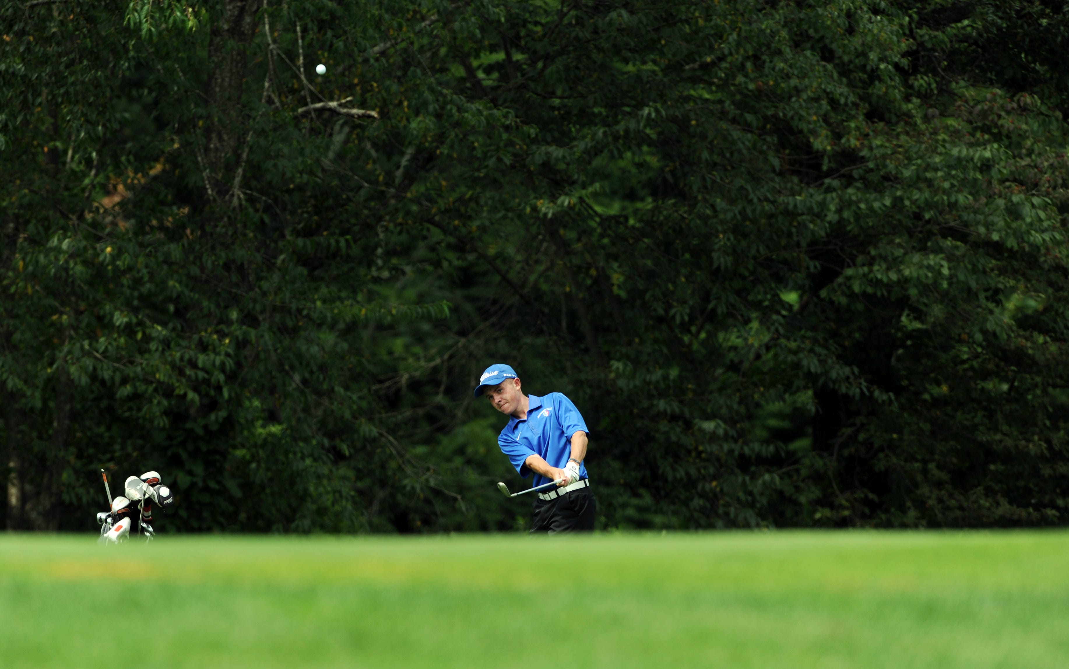 Zanesville junior Harrison Hayes chips onto the 17th green Monday at Zanesville Country Club during the first round of the East Central Ohio League tournament. Hayes and teammate J.J. Burns carded 81s to lead the Blue Devils.