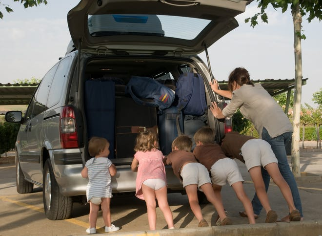 A family (mother and five children) pushing forward their broken down van. The van is fully loaded with their luggage. It is even equiped with a roof box.