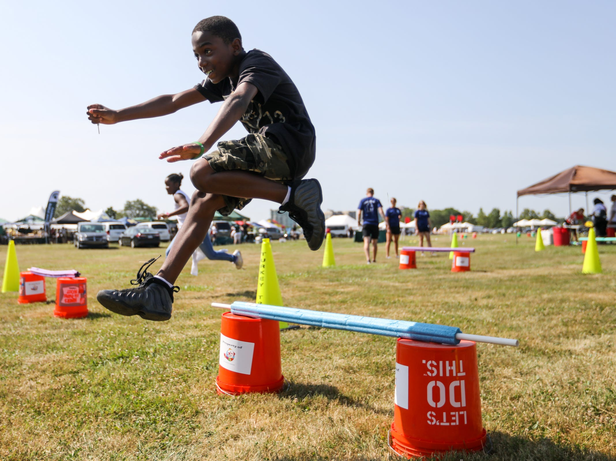 Dishonte Dixon, 11, from George Washington Carver Academy runs a relay race during Metro Detroit Youth Day at Belle Isle in Detroit on Wednesday, July 11, 2018.