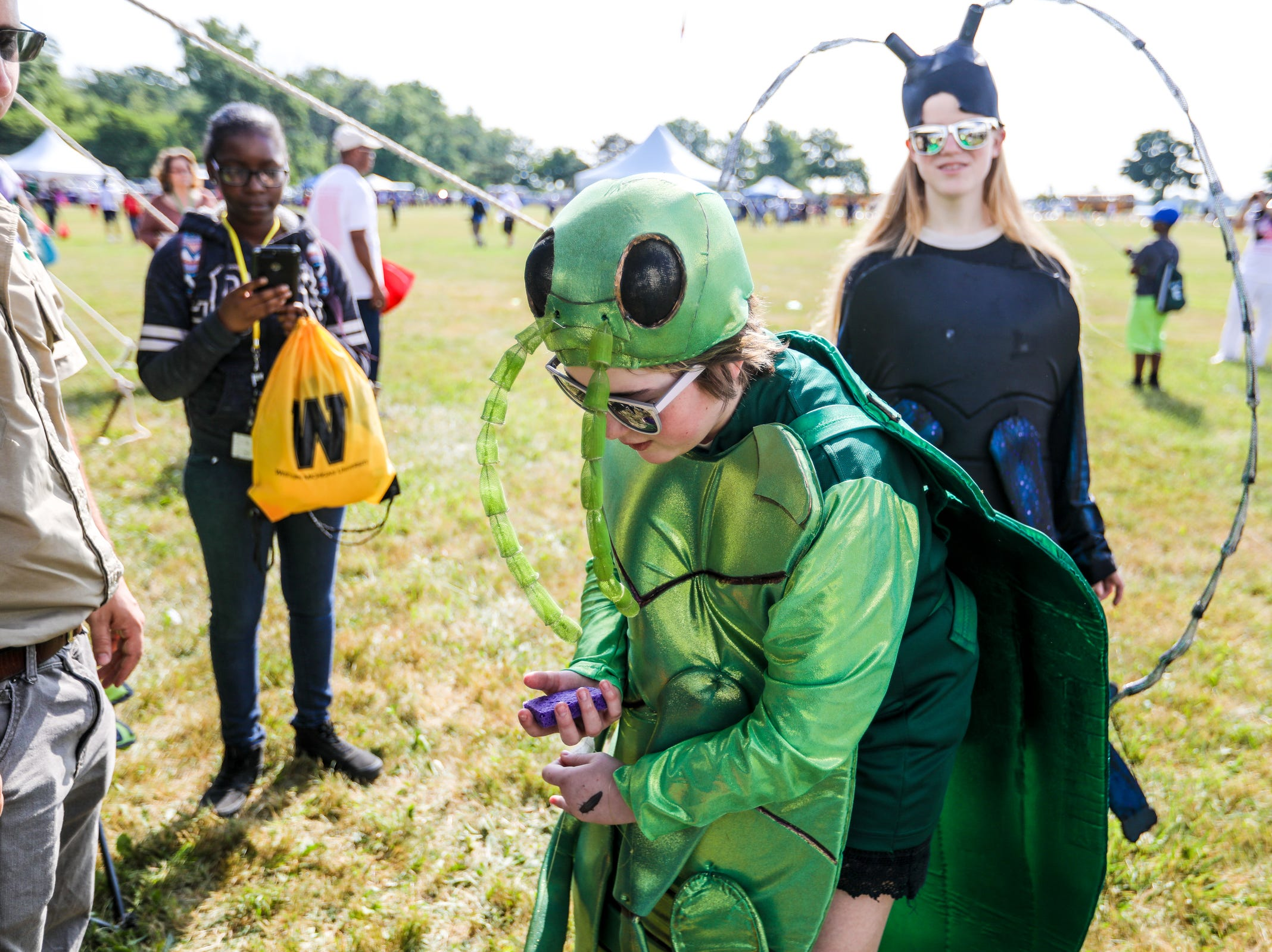 Madison Sullivan, 12, of Milan, dressed as invasive species Emerald Ash Borer as her sister Brianna Sullivan, 15, who is dressed as an Asian Longhorn Beetle, stands by during Metro Detroit Youth Day at Belle Isle in Detroit on Wednesday, July 11, 2018.