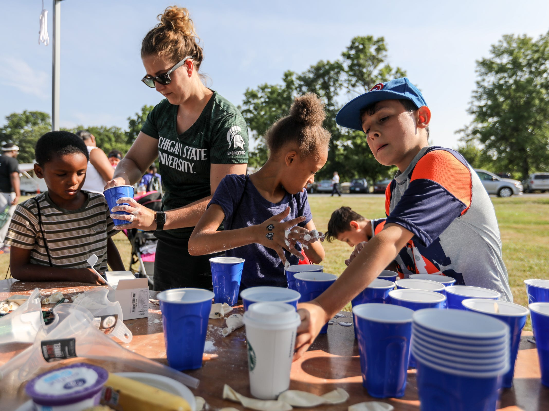 Megan Stadt, 32, of Lansing, who teaches physical science and chemistry at Michigan State University, helps kids make Oobleck during Metro Detroit Youth Day at Belle Isle in Detroit on Wednesday, July 11, 2018.