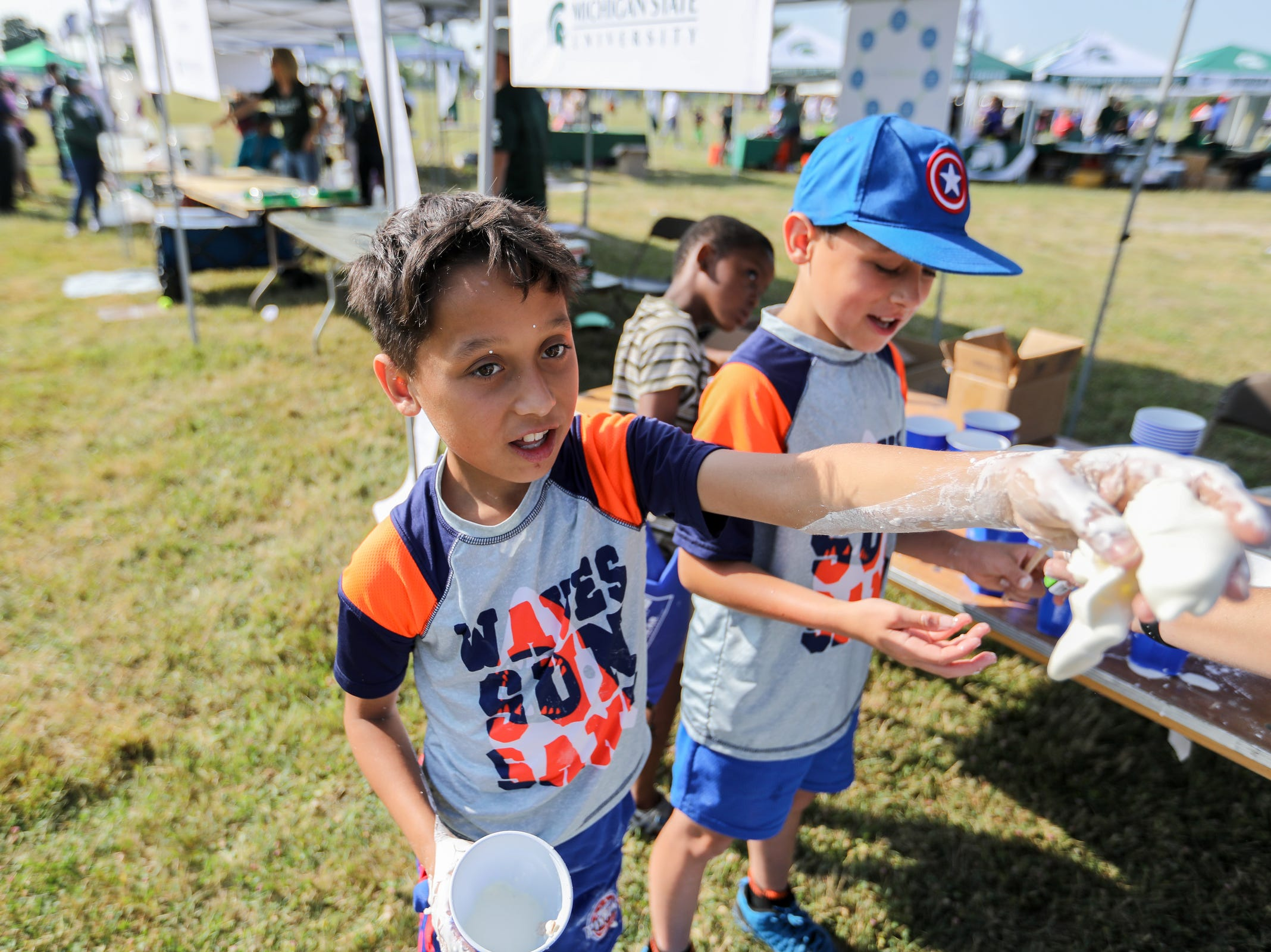 Cody and Dominic Coner, both 10, of Detroit play with Oobleck, a substance typically made of cornstarch and water, during Metro Detroit Youth Day at Belle Isle in Detroit on Wednesday, July 11, 2018.