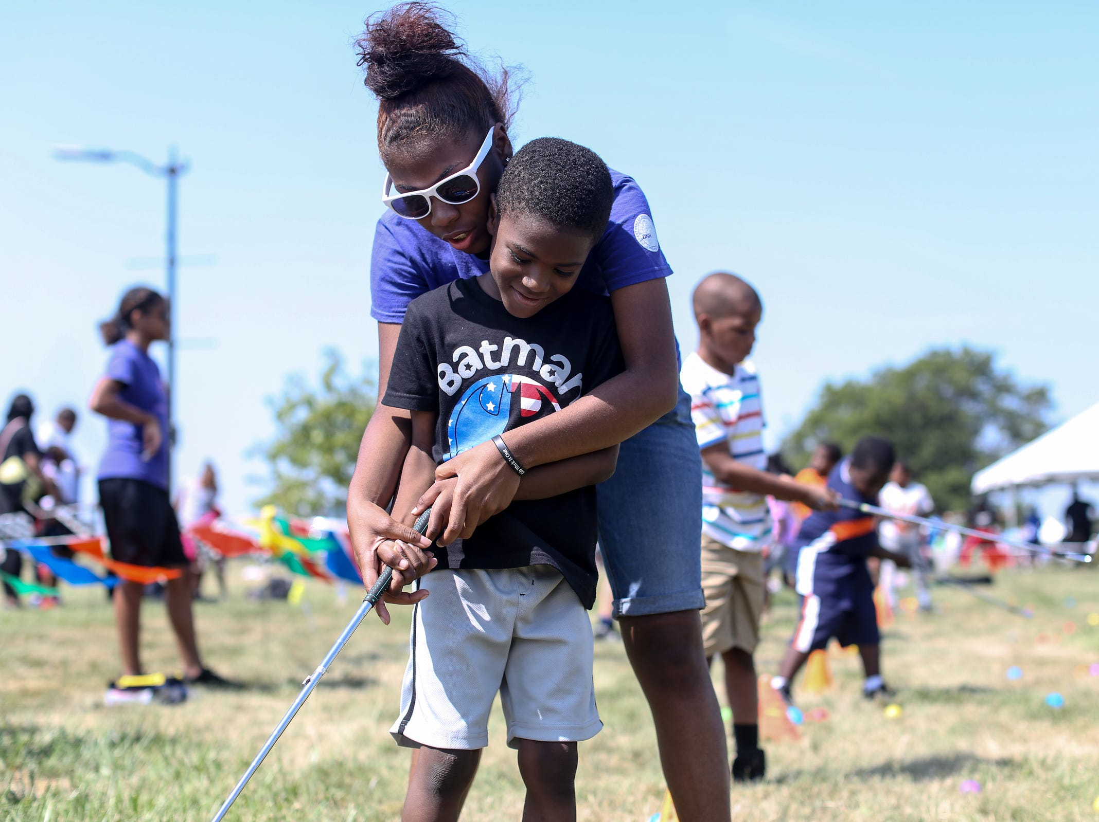 Healthy Kidz, Inc. volunteer Ranneisha Carroll, 17, of Detroit helps Michael Solomon, 6, of Greenfield Union swing a golf club during Metro Detroit Youth Day at Belle Isle in Detroit on Wednesday, July 11, 2018.