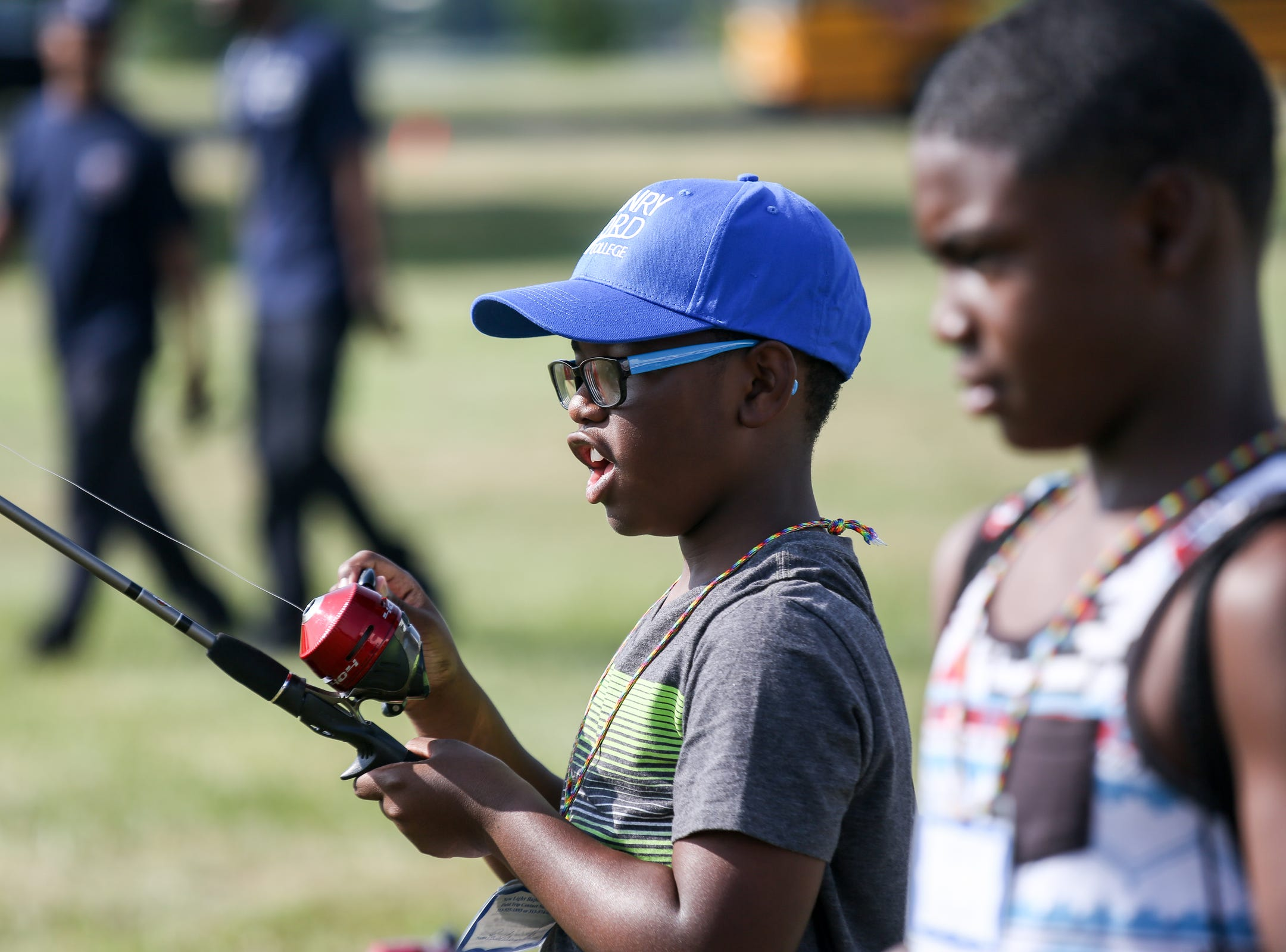 Rashaun William, 12, of Detroit practices casting a fishing pole at the Outdoor Adventure Center's Backyard Bass game during Metro Detroit Youth Day at Belle Isle in Detroit on Wednesday, July 11, 2018.