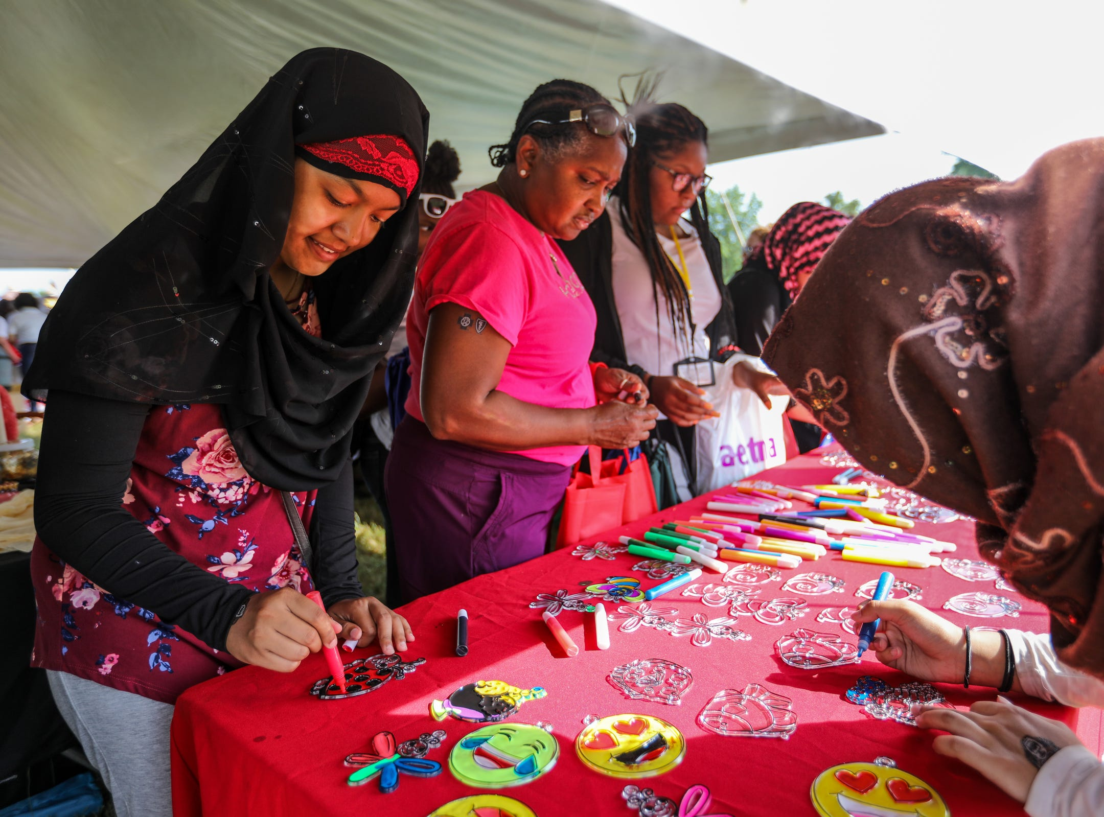 Farhana Chowdhury, 18, of Hamtramck colors in a sun catcher at the VSA Michigan table in the education tent during Metro Detroit Youth Day at Belle Isle in Detroit on Wednesday, July 11, 2018.