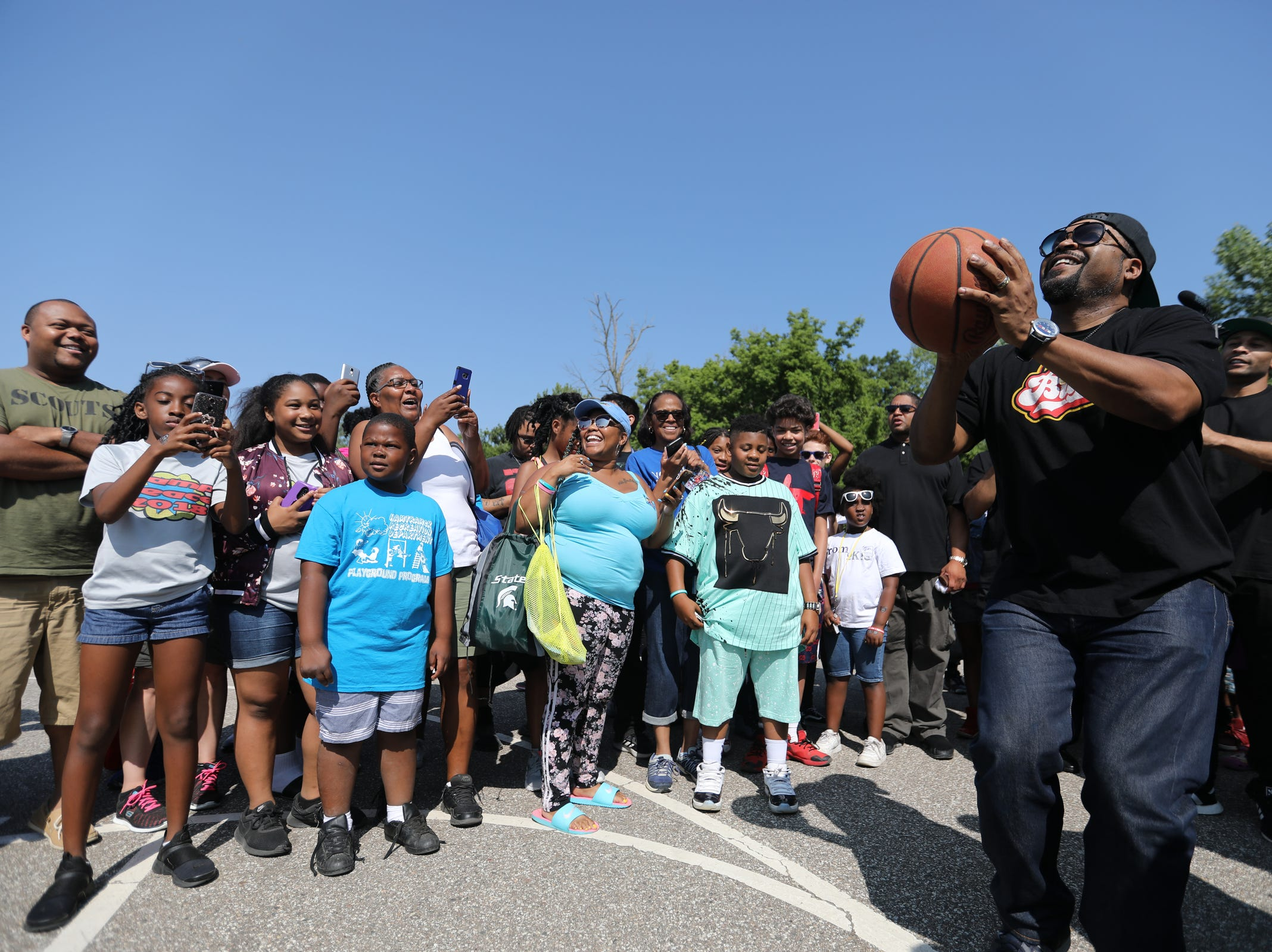 Entertainer Ice Cube attempts a three-point shot surrounded by crowds on a basketball court during Metro Detroit Youth Day at Belle Isle in Detroit on Wednesday, July 11, 2018.