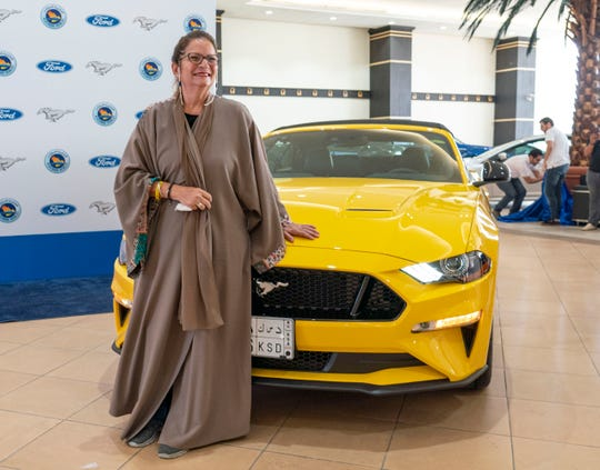 Sahar Hasan Nasif stands with her 2018 Ford Mustang GT convertible.