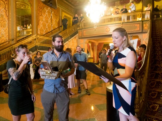 Becky Hancock, right, executive director at the Tennessee Theatre, reads a proclamation from Mayor Madeline Rogero recognizing and congratulating Emily and Sam Brouse as the 2 millionth visitor to the Tennessee Theatre on Tuesday, July 10, 2018.