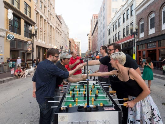 Players shake hands after a game of foosball on Gay St. on Tuesday, July 10, 2018.