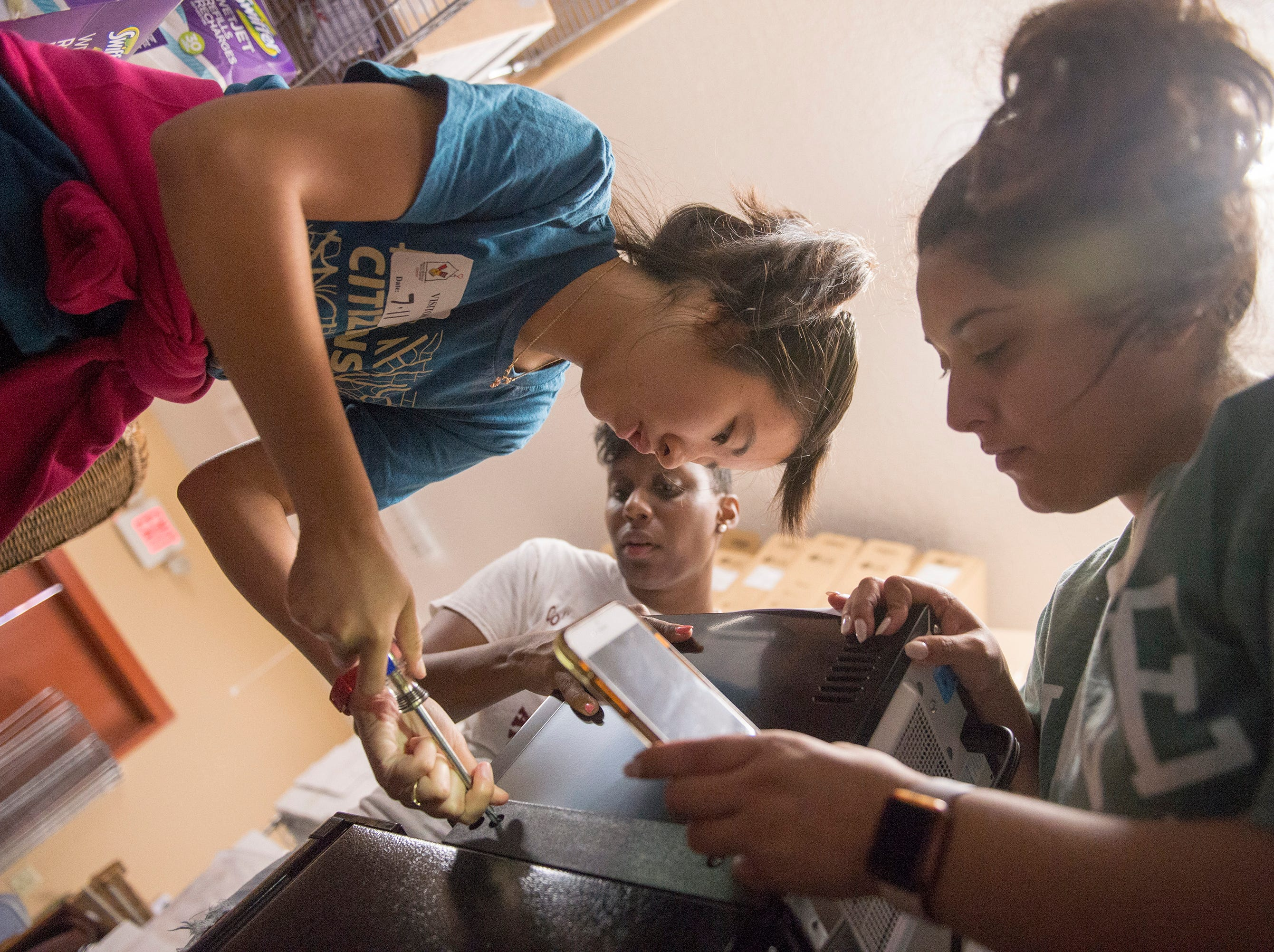 July 11, 2018 - Student volunteers Homerose Uy, left, and Vanessa Brisman, right, work with Memphis Medical District Collaborative organizer Larissa Thompson, center, to assemble combination refrigerator-microwaves for patient families at Ronald McDonald House.