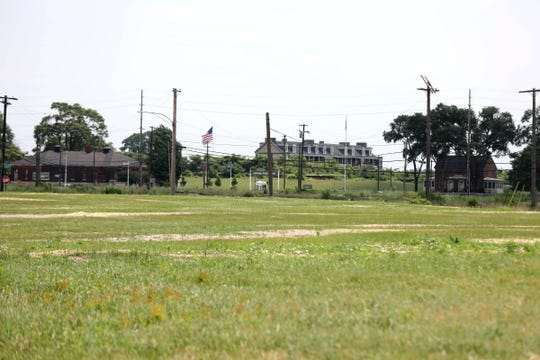 Fort Wayne can be seen in the distance behind the field where 255 building structures, including homes, have been cleared to build the United States Point of Entry plaza, seen during a tour with the Detroit-Windsor Bridge Authority of the proposed sites for the Gordie Howe International Bridge on Thursday, July 5, 2018.