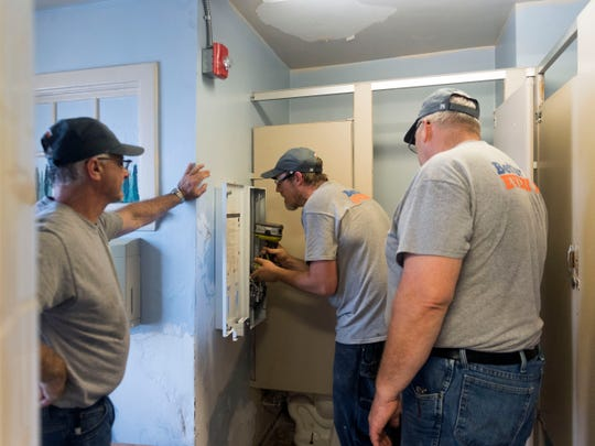 Tranzonic employees Chris Jesmer, left, and Shannon Lytle, right, supervise Adam Campbell as he installs a vending machine that dispenses Maxithin feminine napkins and Tampax tampons in a bathroom at the YWCA on Wednesday, July 11, 2018. The feminine products are provided freely to residents at the YWCA by Tranzonic, which has a factory in Karns that manufactures and distributes a variety of products for public restrooms.